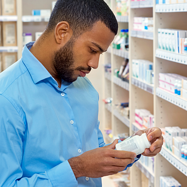 A man reading the label on a bottle of supplements