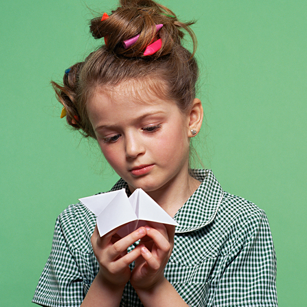 """A young girl holding a paper stress catcher """"fortune teller"""""""