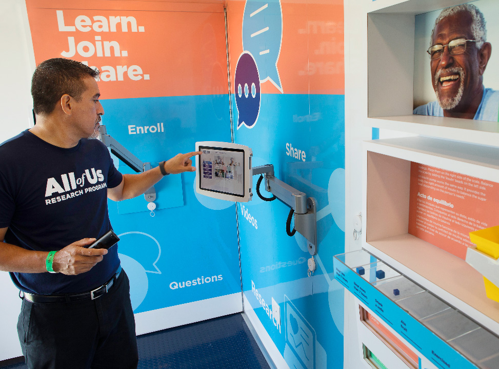 A man interacts with a video kiosk in the All of Us Journey, a traveling exhibit that is visiting communities across the country to raise awareness about the research program. Credit: NIH