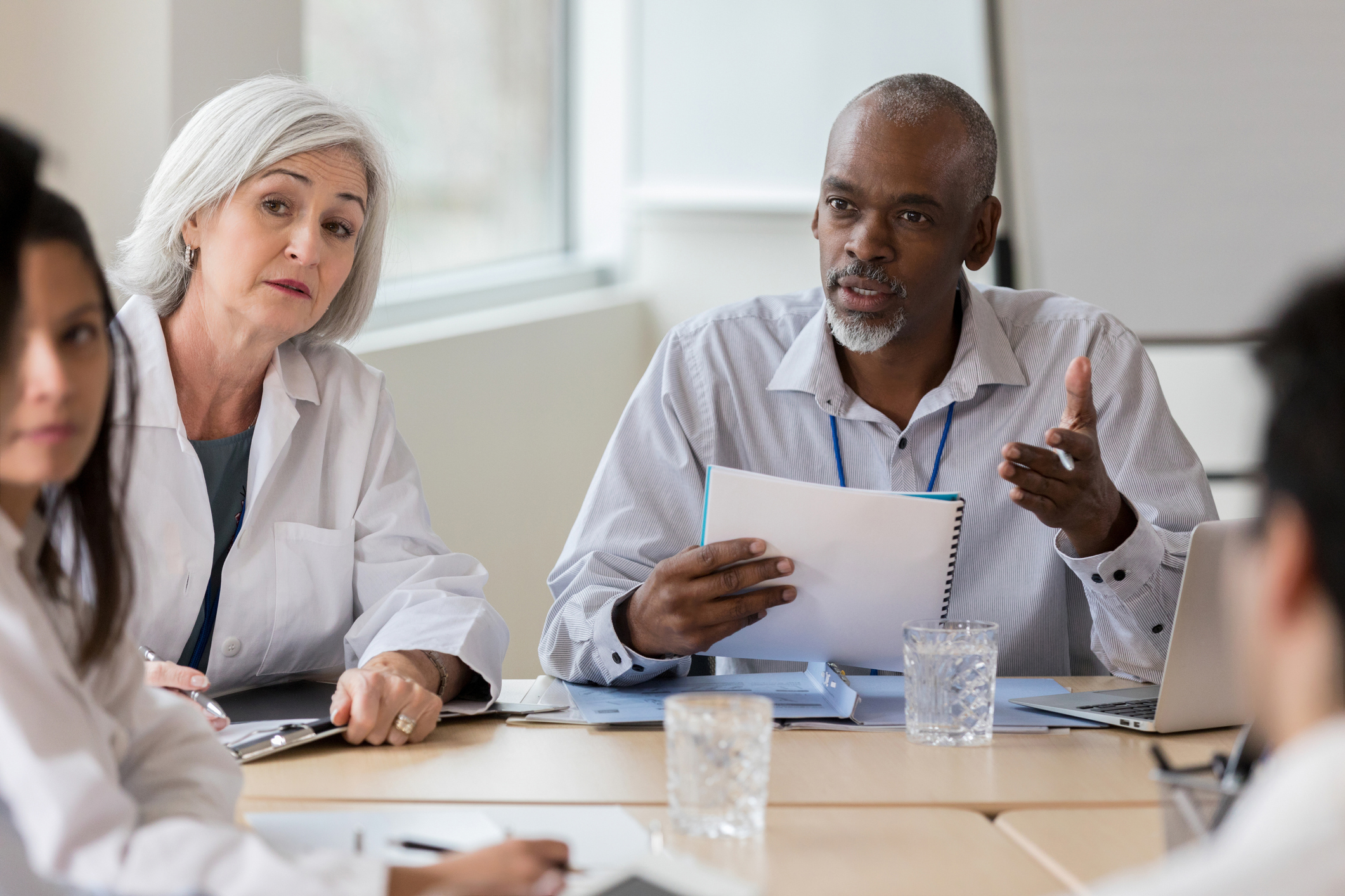 A senior businessman sits at a conference table during a medical staff meeting. He gestures as he speaks seriously with an unrecognizable coworker.