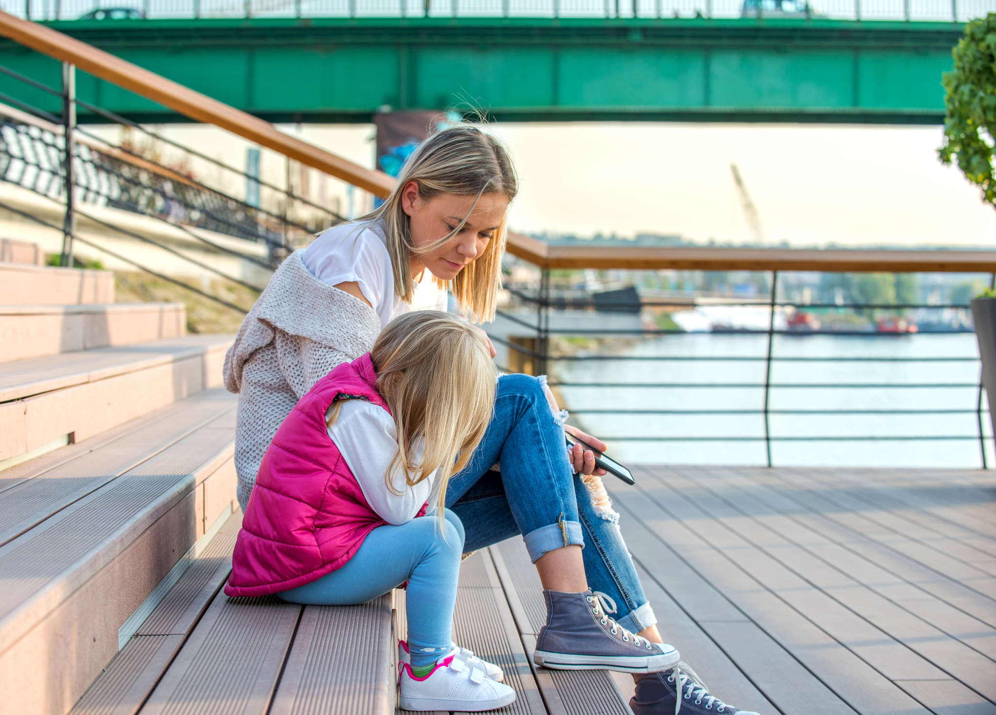 Mother and daughter sitting outside together on stairs