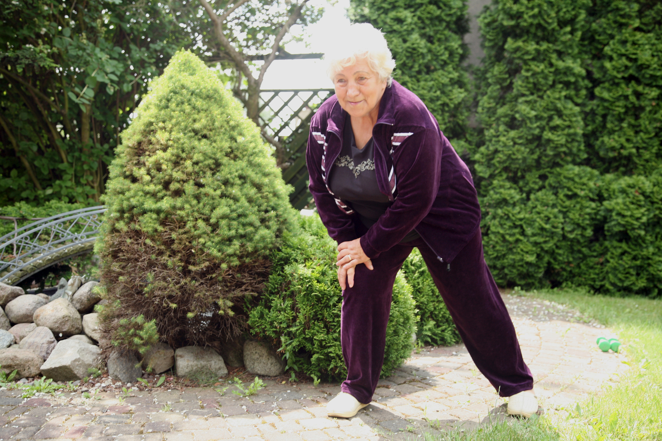 Overweight senior woman exercising in purple velour tracksuitOverweight senior woman exercising in purple velour tracksuit