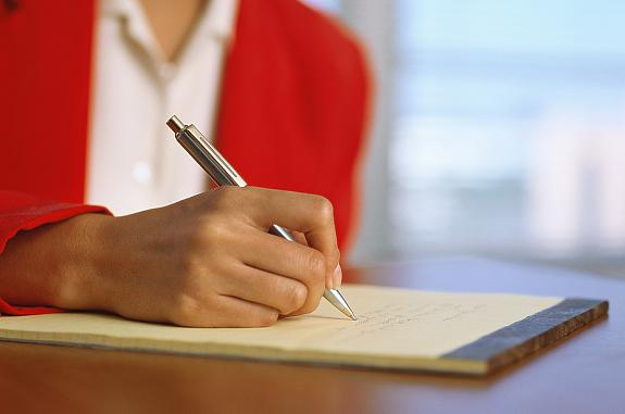 Close-up of a woman writing on a pad.