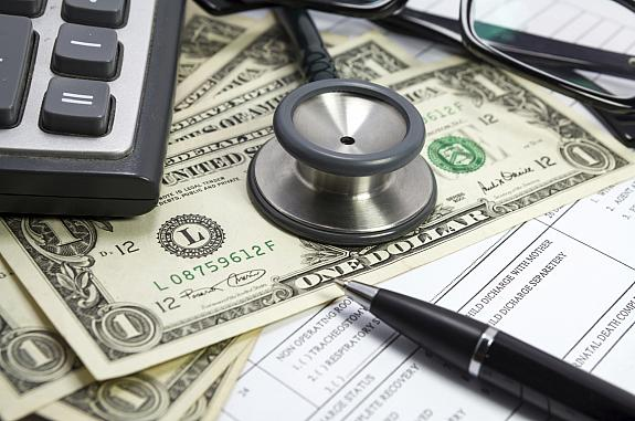 Stethoscope on dollar bills and medical forms.