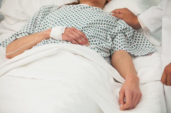 Heath care worker placing a hand on the shoulder of a sick patient in bed