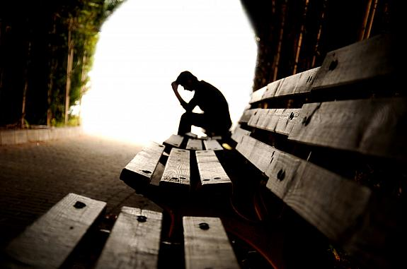 Person sitting alone on a bench in a tunnel.