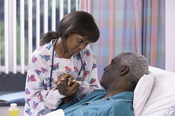Nurse holding the hand of a male patient