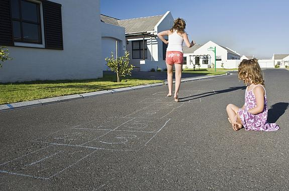 Two girls playing hopscotch on the street