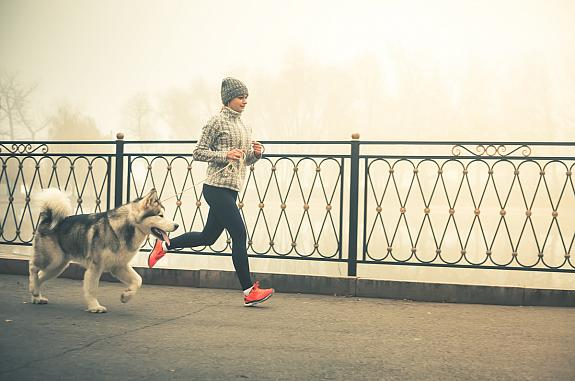 Woman jogging with a dog.