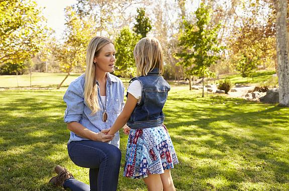 Mother and daughter talking in a park