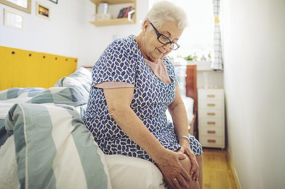 Senior woman holding her knee