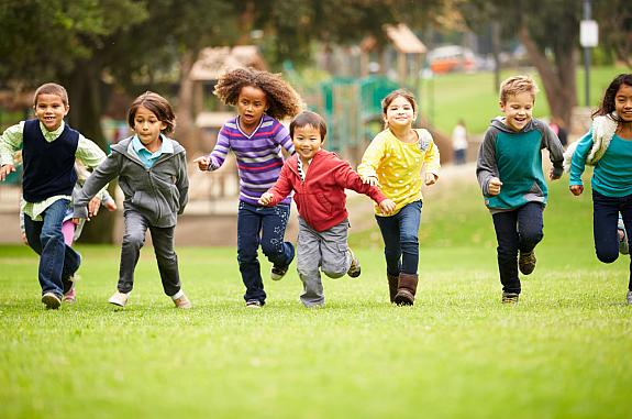 Group of children running over playground grass