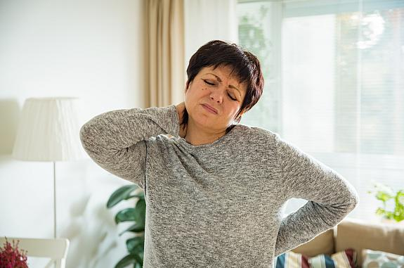 Mature woman holding her back and neck in pain