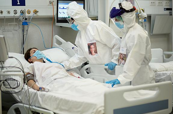 Medical team in protective equipment checking on female patient who is lying in a hospital bed wearing a surgical mask over a breathing device
