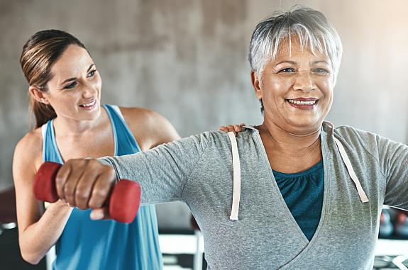 Older woman using weights with a physical therapist