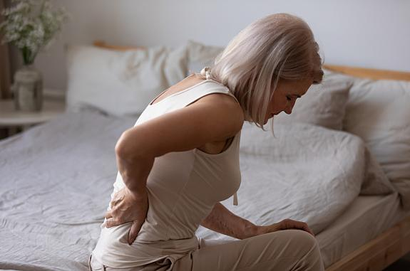Mature woman sitting in bed holding her lower back