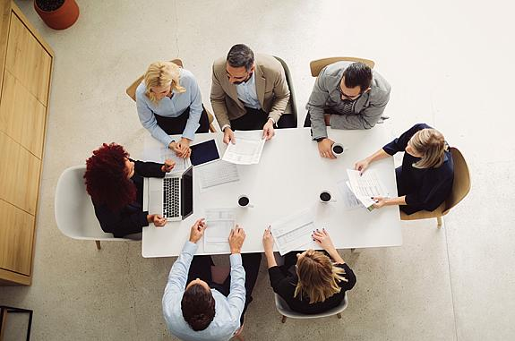 Arial shot of people sitting around a conference table at a meeting