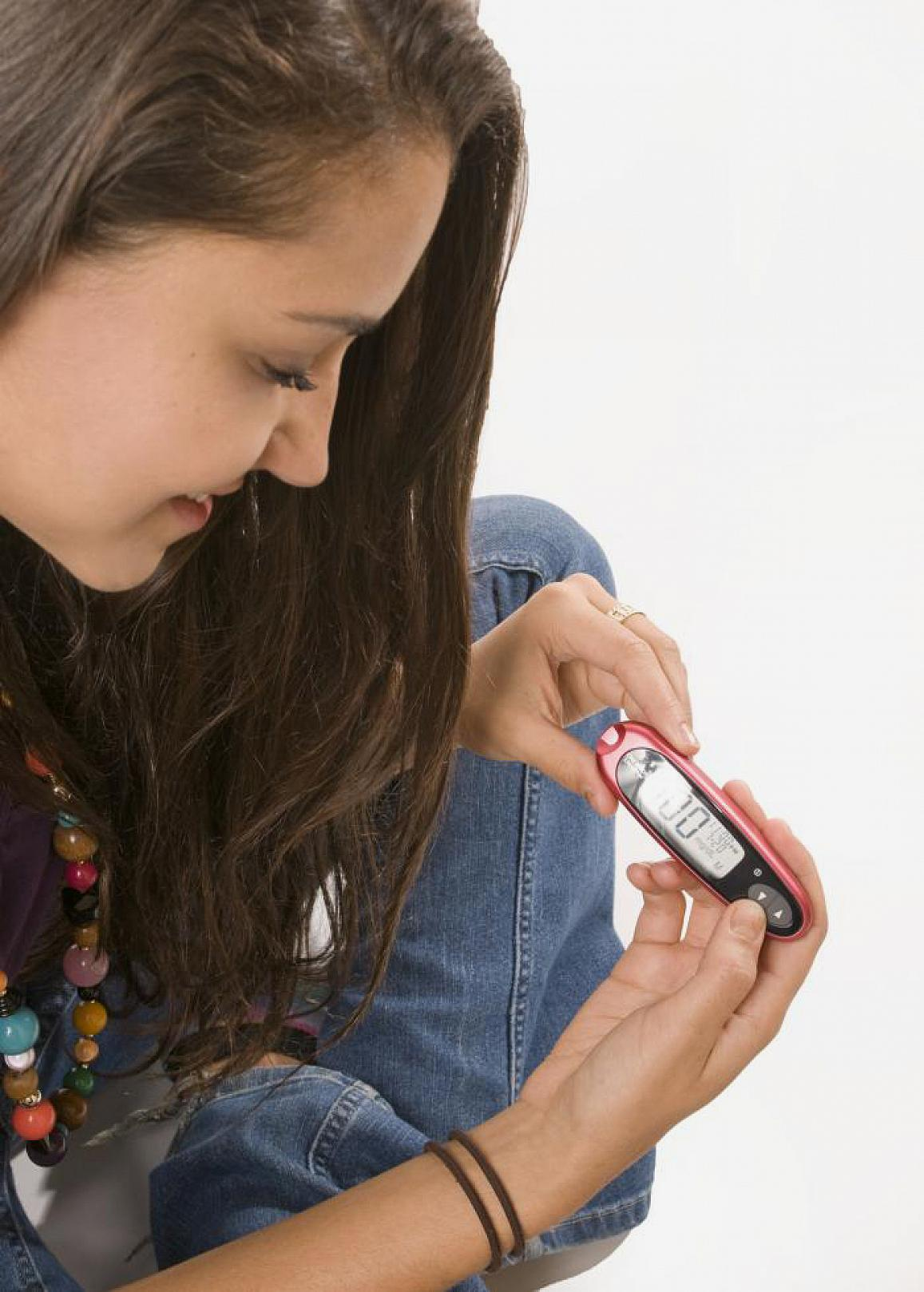 A girl with diabetes checks her blood glucose level.
