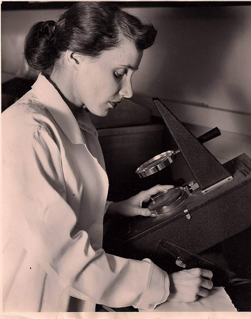 Ruth Kirschstein looking at a microscope.