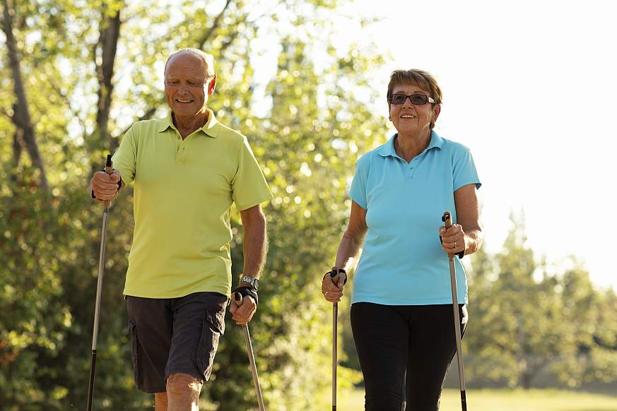 Two active seniors nordic walking outdoors.