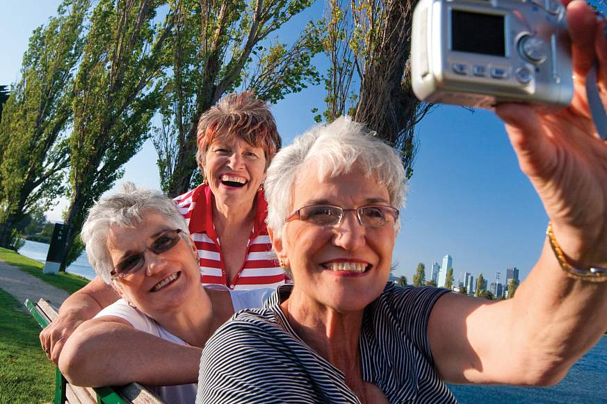 Three older women take a photo of themselves on a park bench.
