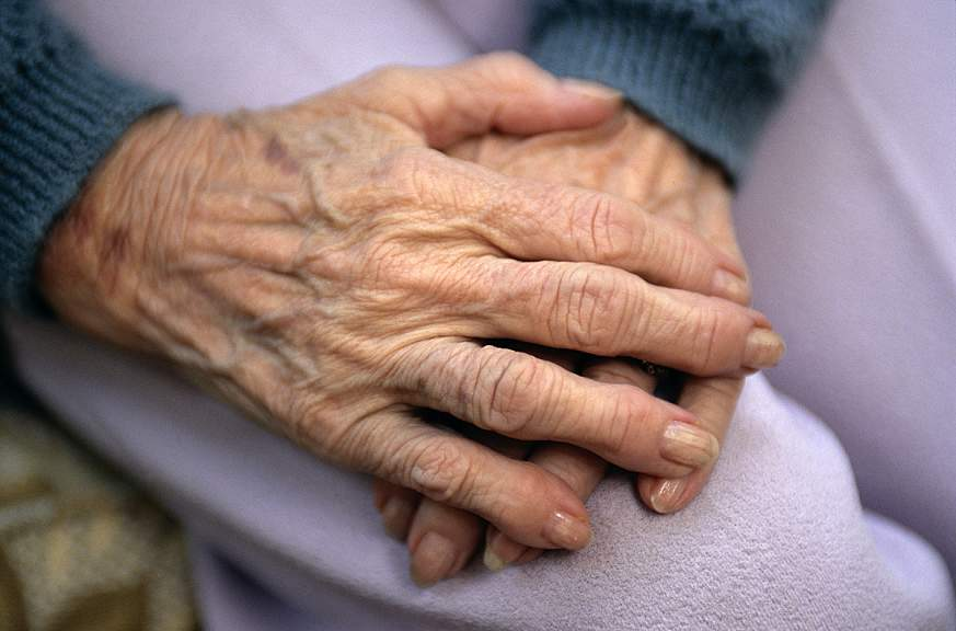 Close-up of an elderly woman's hands resting on her lap.