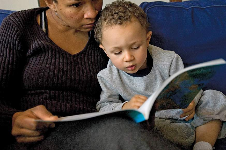 A mother reading to her young son.