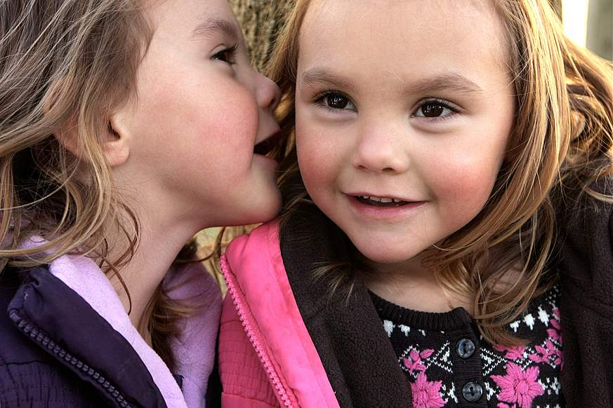 A 3 year old girl whispers a secret into her identical twin sister's ear.