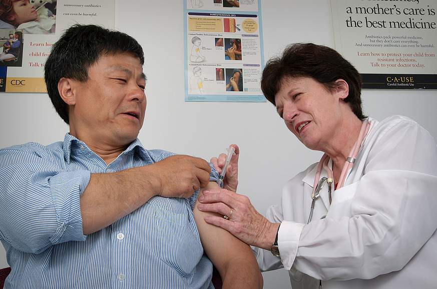 Man receiving an intramuscular immunization in his left shoulder.