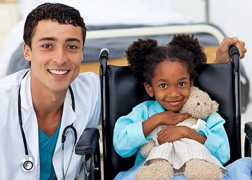 A doctor has his arm around a little girl sitting in a wheelchair and holding a stuffed bear. They are both smiling for the camera.