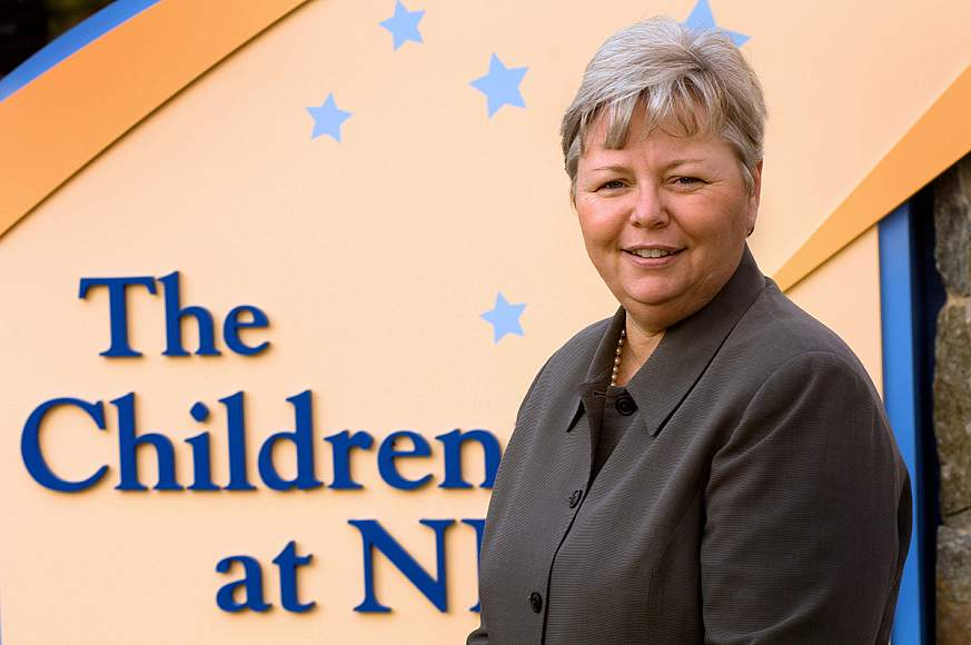 Portrait of Kathy Russell standing in front of the Children's Inn