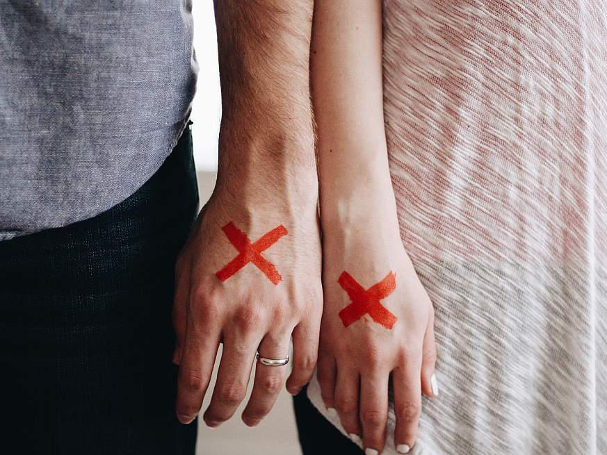 Two people's hands marked with red X's