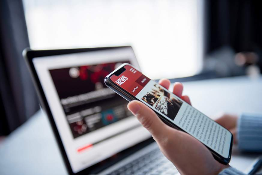 Smartphone and laptop screens showing news