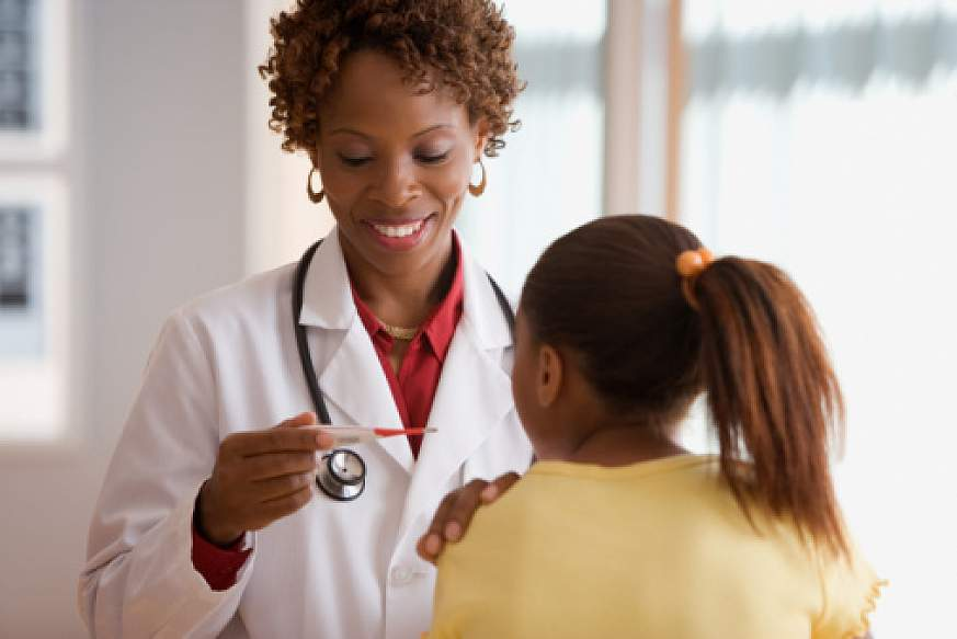 A doctor with a pleasant smile looks at the reading on a thermometer. Her hand is on the patient's shoulder.
