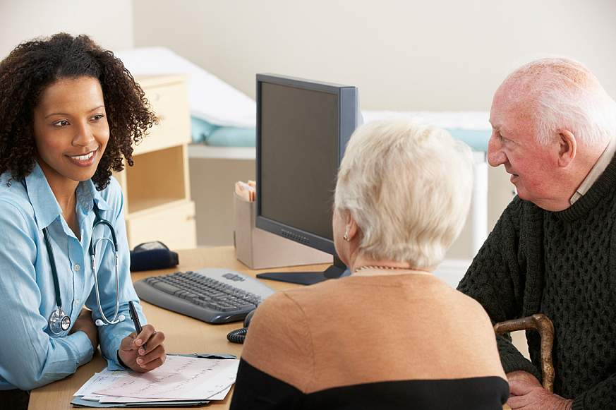 Female doctor talking to a senior couple at her desk.