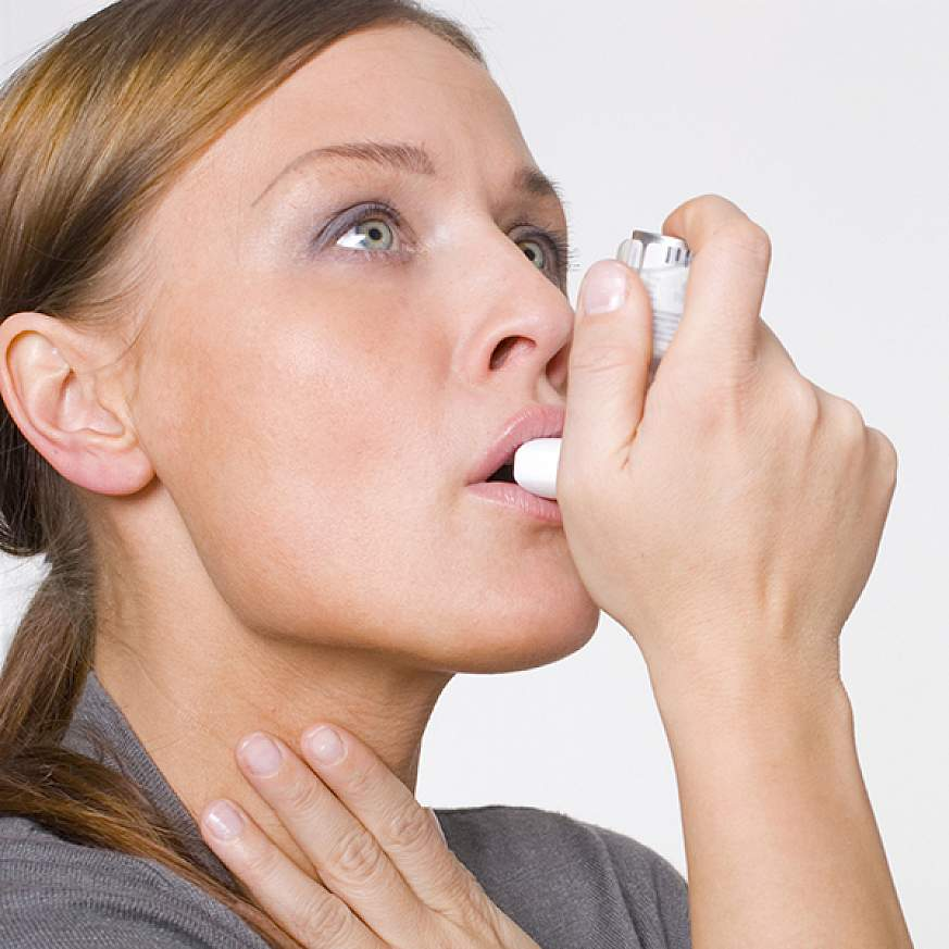 Woman using an inhaler.