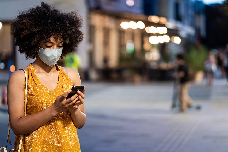 Black women with protective face mask using a smart phone on the street