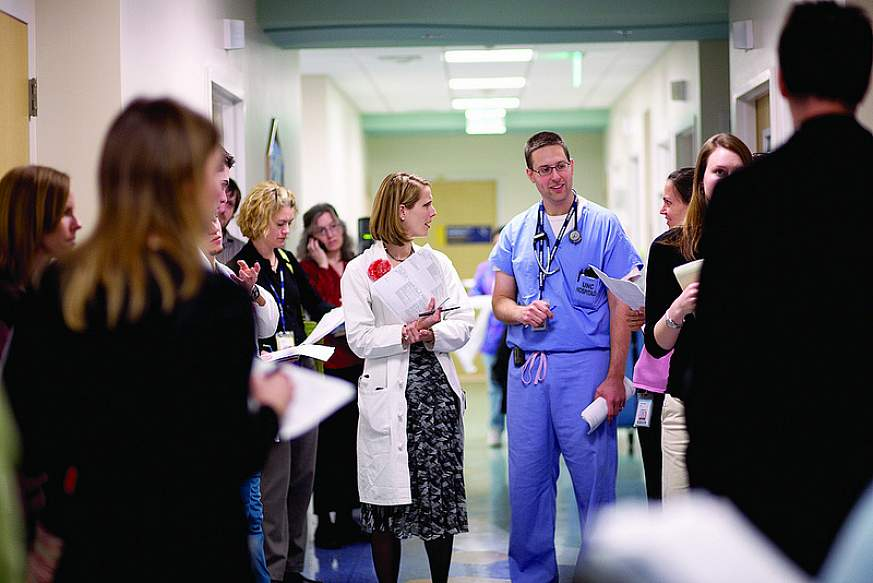 Two doctors in a hospital hallway surrounded by people.