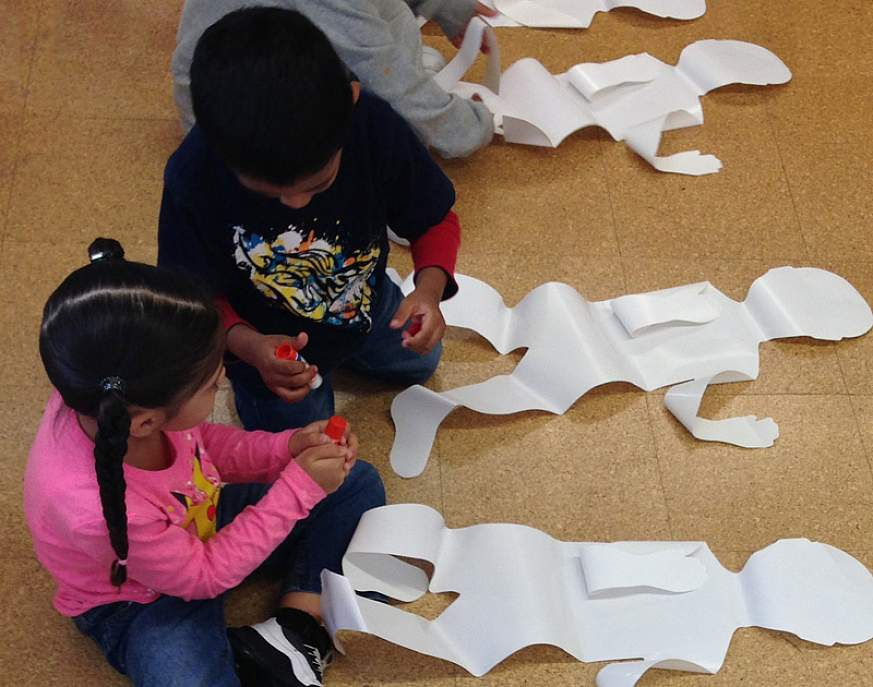 An image of children making body collages. The children will paste vegetables on the corresponding body part that benefits (such as placing two carrots on the eyes). Helps children learn the importance of eating a variety of vegetables every day for good