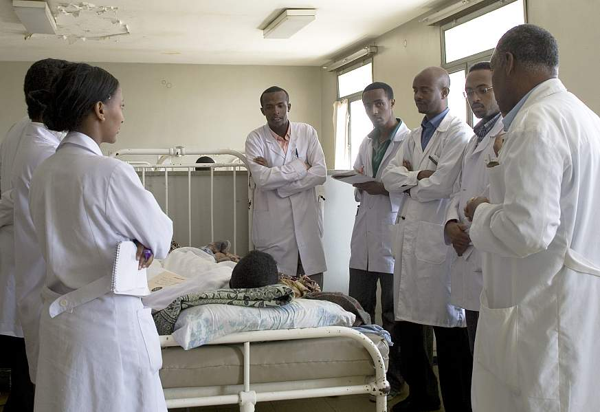 Medical students in white coats gather and discuss around patient bed in hospital