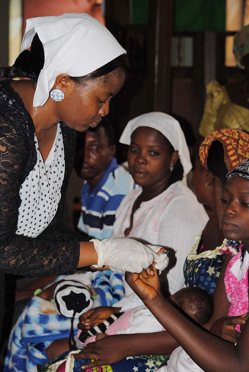 Image of a health worker testing women for HIV.