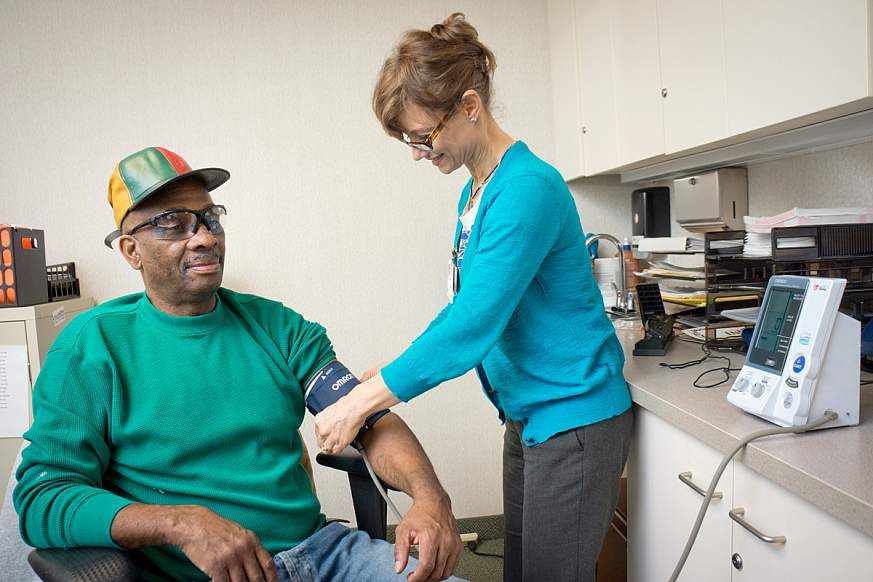 Man gets blood pressure taken by nurse.