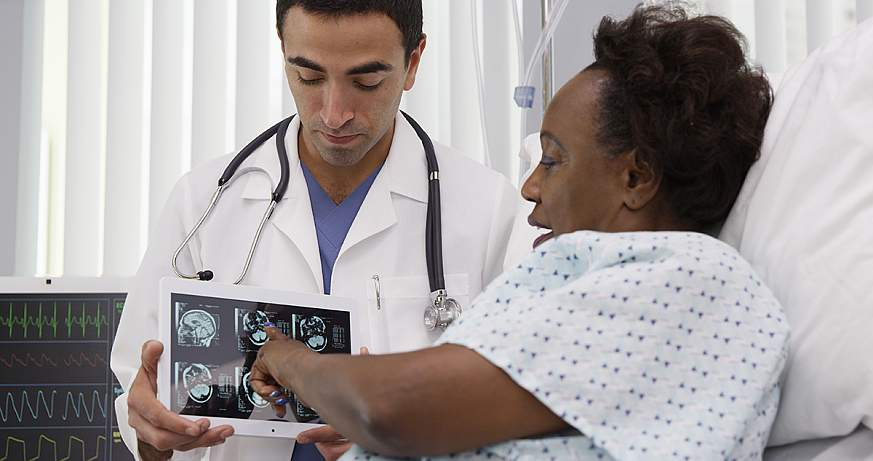 Hispanic doctor showing tablet to patient.