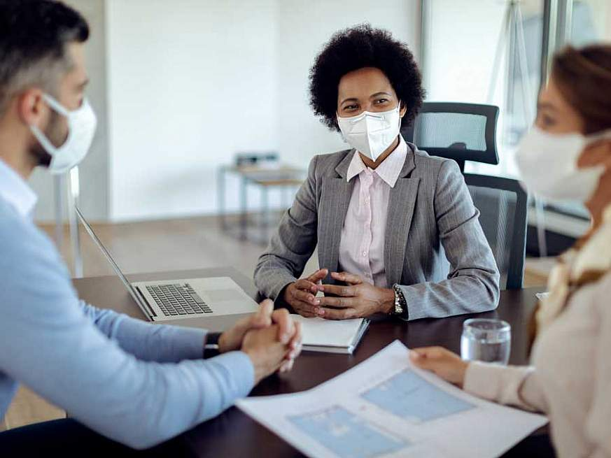 Three seated professionals wearing medical face masks collaborating in an office table.