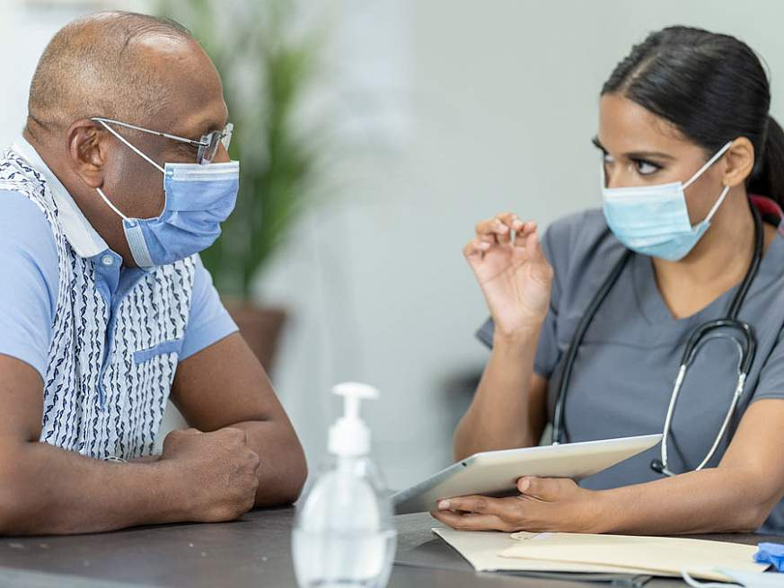 A healthcare worker wearing a medical face mask speaking to a masked patient and referencing a tablet.