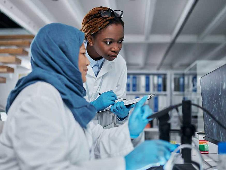 Two women in lab coats analyzing a computer screen in a lab.