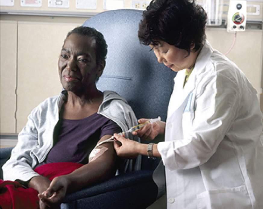 A nurse administering chemotherapy a woman through a catheter.