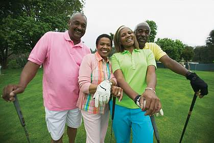 Two adult couples smile for the camera while on the golf course.