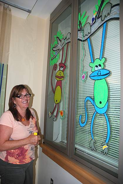 Annette Weller, a self-taught artist, shows a monkey tree she painted on a Clinical Center window.