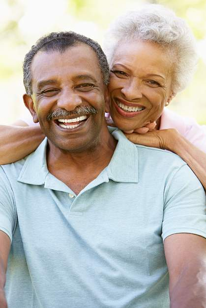 A retired couple smiling for the camera.